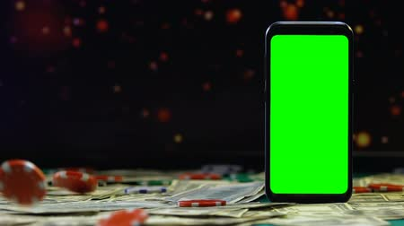főnyeremény : Gaming chips falling on dollars on background of smartphone with green screen Stock mozgókép