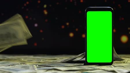 поставщик : Money falling on table around green screen smartphone, earnings on internet Стоковые видеозаписи