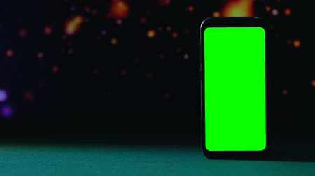 güncelleştirme : Green screen smartphone standing against dark background, casino application