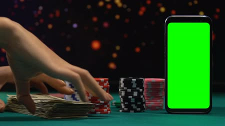 blackjack : Female adding bundle of money to gaming tokens, risky online poker game, all-in