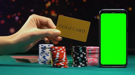 pokerkarten : Woman showing gold card on background of casino chips and green screen phone Videos