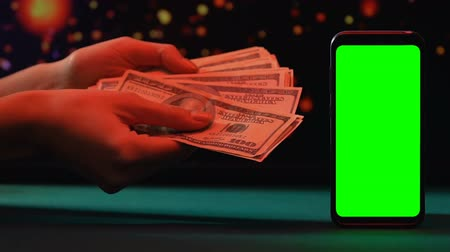 loteria : Person counting dollars near smartphone with green screen, online loans, credit