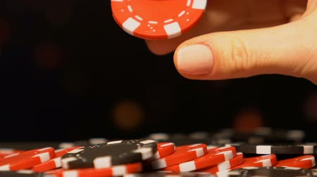 pile of money : Woman taking poker chip from table, rotating in hand, pondering on strategy