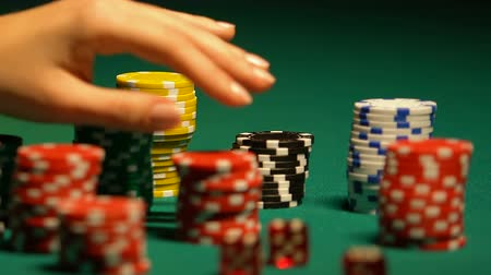 ruletka : Females hand taking poker chip from table, casino bet, gambling addiction
