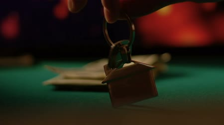 招待状 : Man putting keys from apartment on poker game table, all-in bet, casino concept