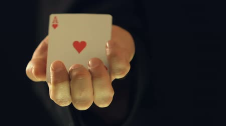 cheat : Man hiding card in his arms, showing ace of hearts into camera, magical trick