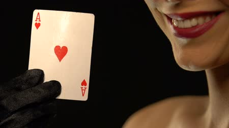 kazık : Smiling lady showing ace of hearts into camera, isolated on black background