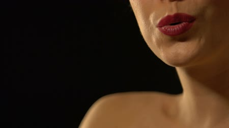 seduce : Beautiful lady sending air kiss into camera, isolated on black background Stock Footage