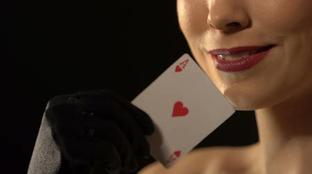 croupier : Flirty woman showing ace of hearts into camera, fortune concept, luxury casino