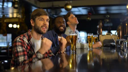 porażka : Male friends drinking beer, cheering for sports game in pub, upset about losing
