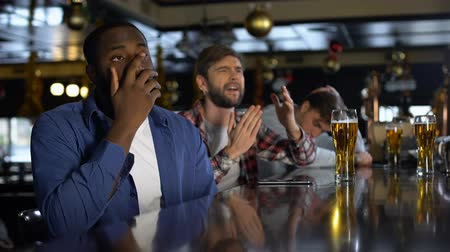 facepalm : Multiracial sport fans watching tournament in pub, disappointed with losing game Stock Footage