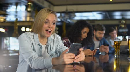 obsession : Millennials using cellphones in bar, addicted to social networks, free wi-fi