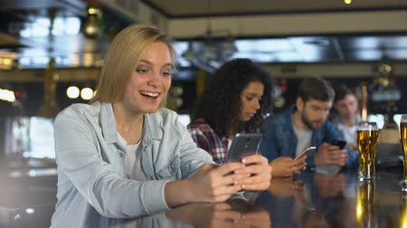 wi fi : Young people using cellphones in bar, reading messages in dating app, free wi-fi