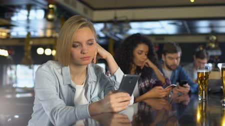 obsession : Young people bored in bar, using phones instead of live communication, addiction Stock Footage