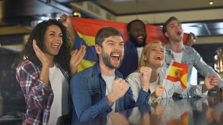 multiethnic : Extremely happy Spanish supporters waving national flag, celebrating victory