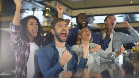 éljenzés : Group of sport fans watching game in bar, rejoicing victory of favorite team