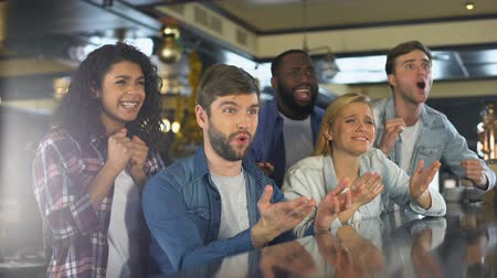 beisebol : Group of friends watching sports program in bar, upset about losing game, defeat Stock Footage