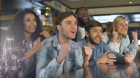 extremely : Group of fans enjoying sport game, extremely happy about win, relaxing in bar