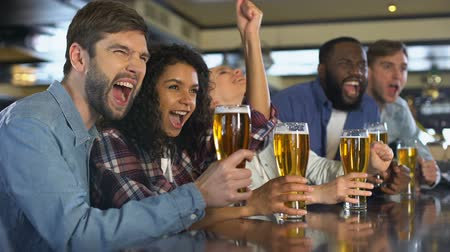tifose : Emotional sport fans clinking beer glasses, celebrating team victory in pub Filmati Stock