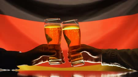 quartilho : Men clinking beer glasses, German flag on background, celebrating festival