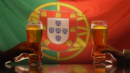 ale : Male friends holding beer glasses, Portuguese flag on background, celebration