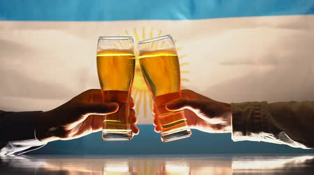 quartilho : Men clinking beer glasses, Argentinian flag on background, national holiday