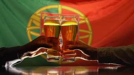 maltês : Male sport supporters clinking beer glasses, Portuguese flag on background Stock Footage
