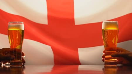 quartilho : Fans holding beer glasses, English flag on background sports team support in pub Stock Footage