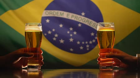 quartilho : Two men holding glasses of beer, Brazilian flag on background, independence day
