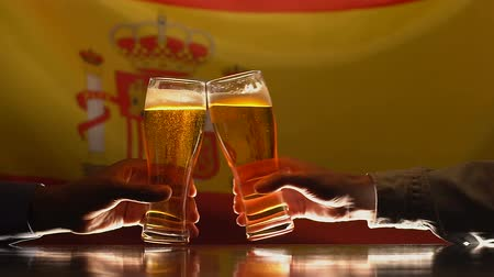 испанский : Men clinking beer glasses, Spanish flag on background, sport fans resting in pub