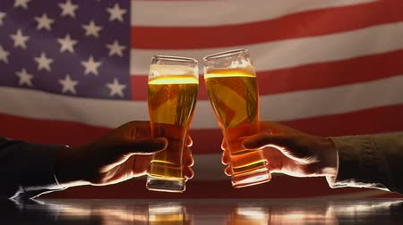 alkoholik : Two men clinking beer glasses against USA flag, independence day celebration