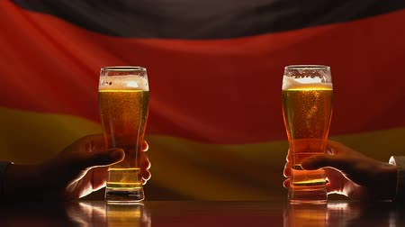 maltês : Two young men holding beer glasses against German flag on background, festival Stock Footage