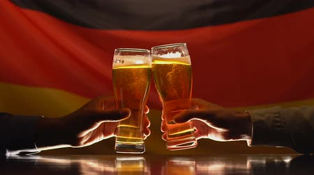 maltês : Two male friends clinking glasses of beer, German flag on background, pub rest