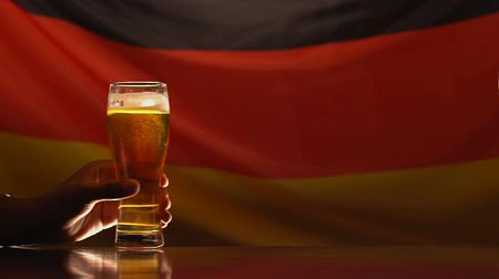pint glass : Two men taking beer glasses, German flag on background, holiday celebration