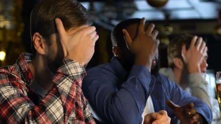 審判 : Male fans watching sport game in pub, making face palm gesture, losing match