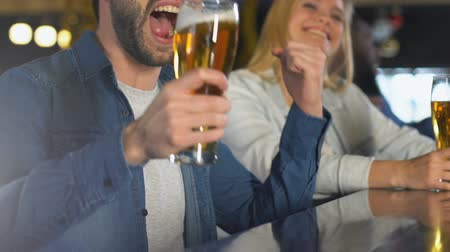 çığlık atan : Young people clinking beer in bar, celebrating favorite sports team victory Stok Video