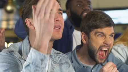 facepalm : Emotional men disappointed about favorite team losing game, evening in pub Stock Footage