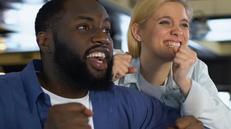ponto : Multiracial couple emotionally watching sport game in bar, cheering for victory