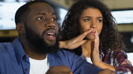 kara : Black couple worrying about sport competition, watching game in pub, leisure Wideo