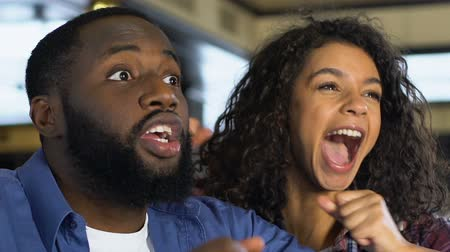 beisebol : Black couple happy about favorite sports team victory, watching game in pub