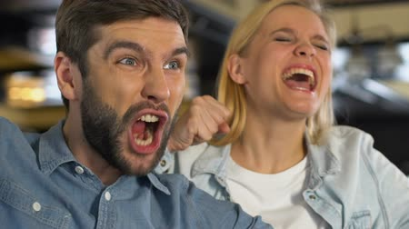 favori : Caucasian couple extremely happy about favorite sports team winning game, league