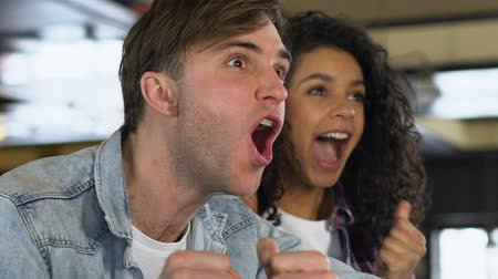 beisebol : Multiracial couple cheering for favorite team victory, watching match in bar Stock Footage