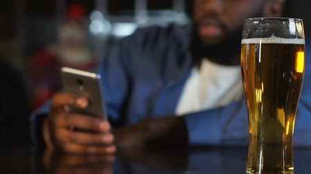 sms : African american man spending time in pub, drinking beer and chatting on phone