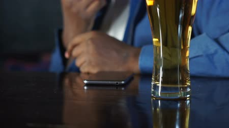 学士 : African american man sitting in sports pub drinking beer and waiting for call 動画素材