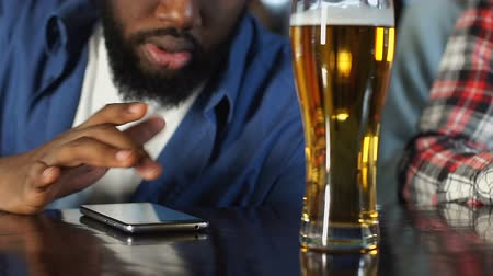 leisure time : African american man making bets in app on his smartphone, watching sports game Stock Footage