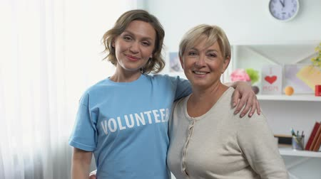 dobrovolník : Mature female and young woman pointing at volunteer inscription on t-shirt Dostupné videozáznamy