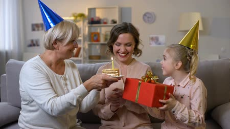 together trust : Young woman celebrating birthday with mother and daughter, family togetherness