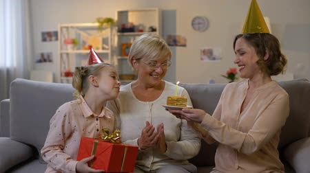 внучка : Female kid and mother in party hats giving present, celebrating granny birthday