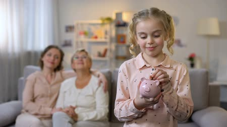 skarbonka : Female kid putting coin piggybank, granny and mother sitting behind, savings