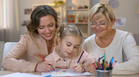 домашнее задание : Happy child with mother and granny drawing pencils smiling on camera, family